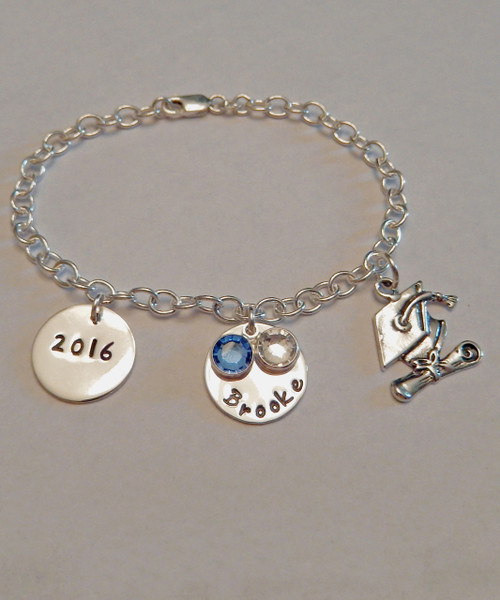 "Hand Stamped 2016 Graduation Charm Bracelet with ""2016"" Charm,  Personalized Name Charm, Two Genuine Swarovski Birthstones, and Cap & Diploma Charm, all in Solid Sterling Silver. It is shown with a polished finish. Choose from five custom finish options. Use the drop down menu if you would like to add more charms. Use the drop down menu if you would like to add Genuine Swarovski Birthstones.   SIZE: Choose 7"", 8"", or 9"" Bracelet Length 4mm width Solid Sterling Silver Charm Bracelet One Solid Sterling Silver 5/8"" Round stamped, ""2016."" One Solid Sterling Silver 5/8"" Round Charm with name of choice. Two Swarovski Crystals choice of colors. (Graduation Colors of Blue & White if choice left blank) One Solid Sterling Silver Cap and Diploma Charm."