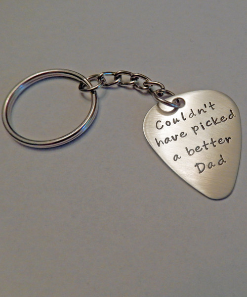 """""""Couldn't have picked a better Dad"""" Guitar Pick Key Chain. Shown with a Brushed Finish in Solid Nickel. Guitar Pick in choice of Solid Nickel, Solid Copper, Solid Brass, or Solid Sterling Silver. Choose from five custom finish options. Double Sided Text Optional.    SIZE: Approx. 1"""" x 1 1/4"""" Guitar Pick"""