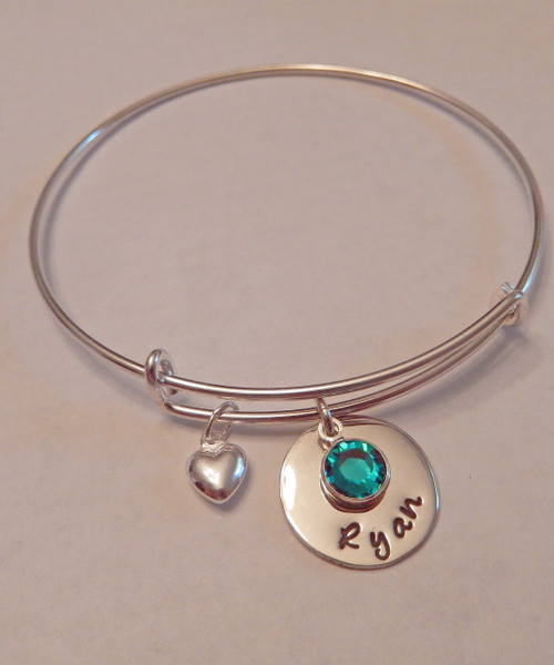 "Hand Stamped Round Name Charm with Genuine Swarovski Birthstone on Expandable Bangle Bracelet all Sterling Silver. One size fits most. It is shown with a Polished Finish. Included is one puffy heart charm , Name Charm and one Genuine Swarovski Birthstone. Choose from five custom finish options. Use the drop down menu if you would like to add more charms or Genuine Swarovski Birthstones.   SIZE:  Expandable one size fits all 2 1/2""-3"" Solid Sterling Silver Bangle Bracelet 1.5mm. One Solid Sterling Silver puffy heart charm One Solid Sterling Silver 5/8"" Round Charm. One Genuine Swarovski Crystal Birthstone choice."
