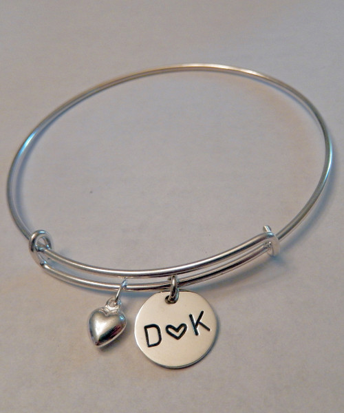 "Expandable Bangle Bracelet Hand Stamped Initial-Heart-Initial Charm and Puffy Heart, all Sterling Silver. One size fits most. It is shown with a Polished Finish. Choose from five custom finish options. Use the drop down menu if you would like to add name charms. Use the drop down menu if you would like to add Genuine Swarovski Birthstones.    SIZE:  Expandable one size fits all 2 1/2""-3"" Solid Sterling Silver Bangle Bracelet 1.5mm. One Solid Sterling Silver puffy heart charm One Solid Sterling Silver 1/2"" Round Charm."