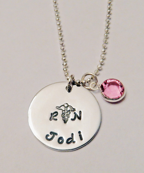 """RN or LPN Nurse Necklace Hand Stamped with Name & Genuine Swarovski Crystal Birthstone, all Sterling Silver Necklace. It is shown with a Polished Finish on a Diamond Cut Bead Chain. Choose from five custom finish options. Use the drop down menu to add Genuine Swarovski Birthstones.  SIZE: 3/4"""" Solid Sterling Silver Round with RN, Symbol, and Name One Genuine Swarovski Crystal Birthstone choice"""