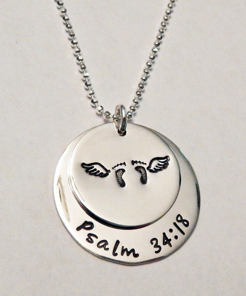 """Stamped Infant Loss Necklace ~ Sterling Silver Child Memorial Necklace ~ """"Psalm 34:18"""" Baby Feet & Angel Wings Remembrance Necklace. It is shown with a Polished Finish on a Diamond Cut Bead Chain. Choose from five custom finish options. You can have a Date or Name below the baby feet if you like, or customize the text on the larger piece of silver. Use the drop down menu to add Genuine Swarovski Birthstones.  Psalm 34:18 NIV  The Lord is close to the brokenhearted and saves those who are crushed in spirit.  SIZE: Solid Sterling Silver 1"""" Round with """"Always in my heart"""" or custom text Solid Sterling Silver 3/4"""" Round with baby feet and angel wings (optional name, date, other custom text)"""