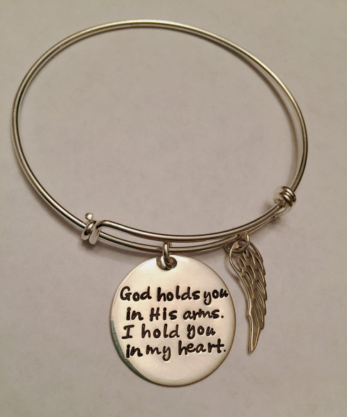 """Hand Stamped Round """"God holds you in His arms, I hold you in my heart."""" Expandable Bangle Bracelet & Angel Wing Charm, all .925 Sterling Silver. Memorial Bracelet, one size fits most. It is shown with a Polished Finish on a Solid Sterling Silver Bangle. Choose from five custom finish options. Use the drop down to add Genuine Swarovski Birthstones.   SIZE:  Expandable one size fits all 2 1/2""""-3"""" Solid Sterling Silver Bangle Bracelet 1.5mm. One Solid Sterling Silver 1"""" Round stamped, """"God holds you in His arms, I hold you in my heart."""" One Solid Sterling Silver Angel Wing Charm."""