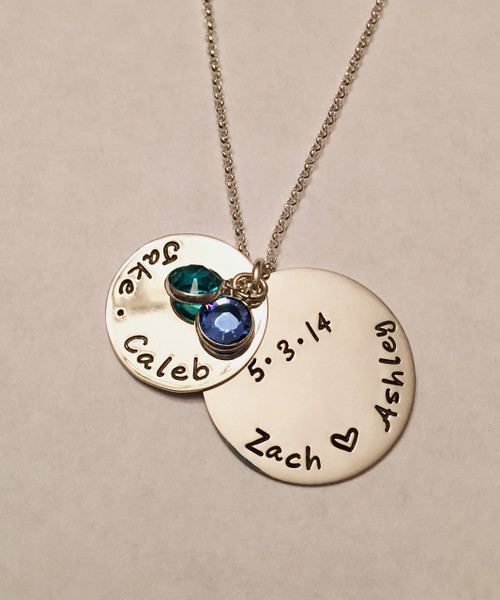 """Hand Stamped Sterling Silver Family Name Necklace with Peek-a-Boo Anniversary Date with Swarovski Birthstone. One Birthstone is included. Shown with a Polished Finish on a Solid Sterling Silver Rolo Chain. Choose from five custom finish options. Use drop down menu to add Genuine Swarovski Birthstones. SIZE: Solid Sterling Silver 1"""" Round with names of Dad & Mom with a heart in the middle or custom text Solid Sterling Silver 3/4"""" Round with names of children separated by a dot, or custom text One Swarovski Birthstone (Choice of Color)"""