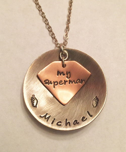 "Husband Memorial Superman Necklace. Hearts can replace wings if you do not require a memorial piece. Round Large Domed 1 1/4"" Sterling Silver Pendant with Name & Angel Wings shown with an Aged Finish stacked with a Domed Copper ""my superman"" logo shown with a Brushed Finish on an Oxidized Cable Chain. Choose from five custom finish options. Use the drop down menu to add Genuine Swarovski Birthstones. *Please specify when checking out if you would like two finishes as shown because when you choose a finish, the entire necklace comes in that finish unless otherwise specified.    SIZE:  Solid Sterling Silver Domed 1 1/4"" Round stamped with name & angel wings or custom text Solid Coper Domed Superman Logo shape stamped ""my superman"" or other custom text"