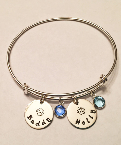 """Hand Stamped Dog Paw/Cat Paw Charm with Pet Name and Genuine Swarovski Birthstone on Expandable Bangle Bracelet all Sterling Silver. One size fits most. It is shown with a Polished Finish on a Solid Sterling Silver Bangle. One Circle Name Charm & one Birthstone are included. Choose from five custom finish options. Use the drop down menu to add Solid Sterling Silver Name Charms. Use the drop down menu if you would like to add Genuine Swarovski Birthstones.   SIZE:  Expandable one size fits all 2 1/2""""-3"""" Solid Sterling Silver Bangle Bracelet 1.5mm. One Solid Sterling Silver 5/8"""" Round Charm. One Swarovski Crystal Birthstone choice."""