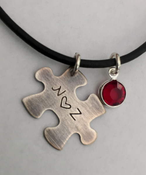 """Jigsaw Puzzle Piece Stamped Initial-Heart-Initial, all Sterling Silver Autism Awareness with Genuine Swarovski Birthstone and choice of chain. It is shown with an Aged Finish on a Black Leather Chain with Solid Sterling Silver Findings. Choose from five custom finish options.The Swarovski Crystal can be blue for autism awareness if you like. Use the drop down menu to add Genuine Swarovski Birthstones.   SIZE: Solid Sterling Silver 24 gauge Jigsaw Puzzle Piece approx. 4/5"""" x 1/2"""" One Genuine Swarovski Crystal Birthstone choice"""