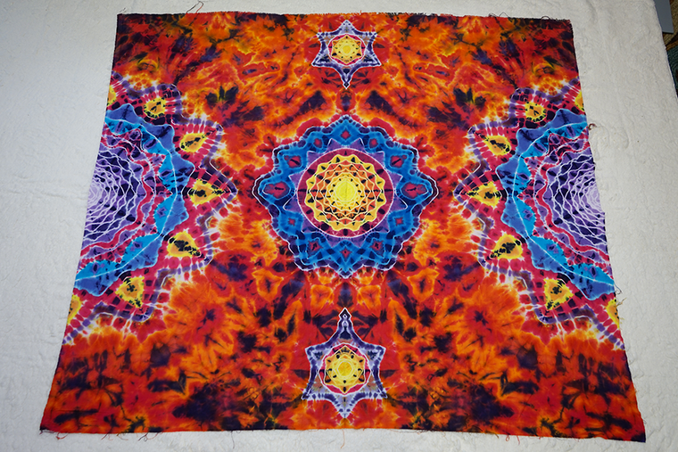 Smaller tie dye tapestry with a unique design, reds oranges and blues