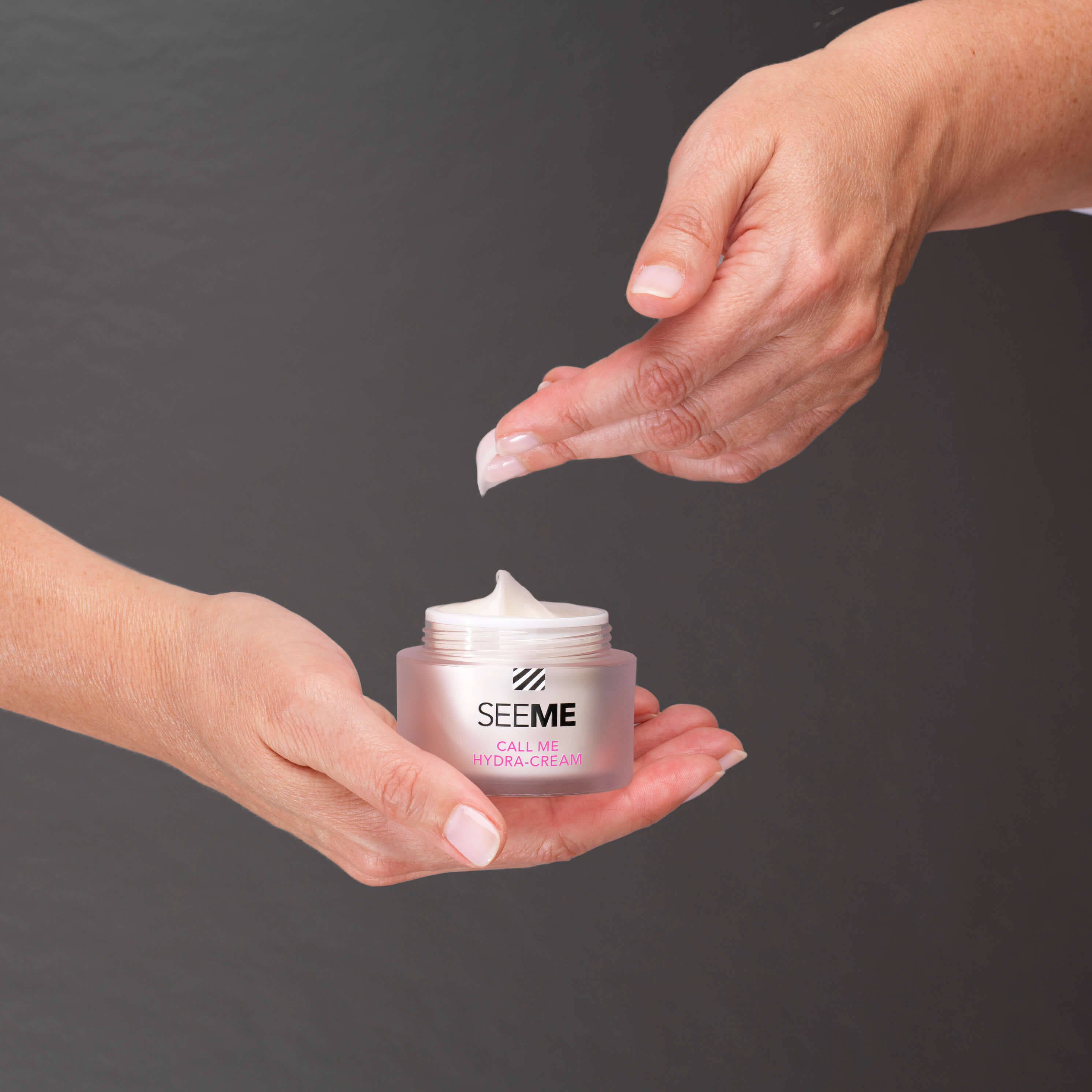 SeeMe Call Me Hydra-Cream with SeeMe Complex. Image of woman dipping the light airy moisturizer from the jar she is cradling in her hand.