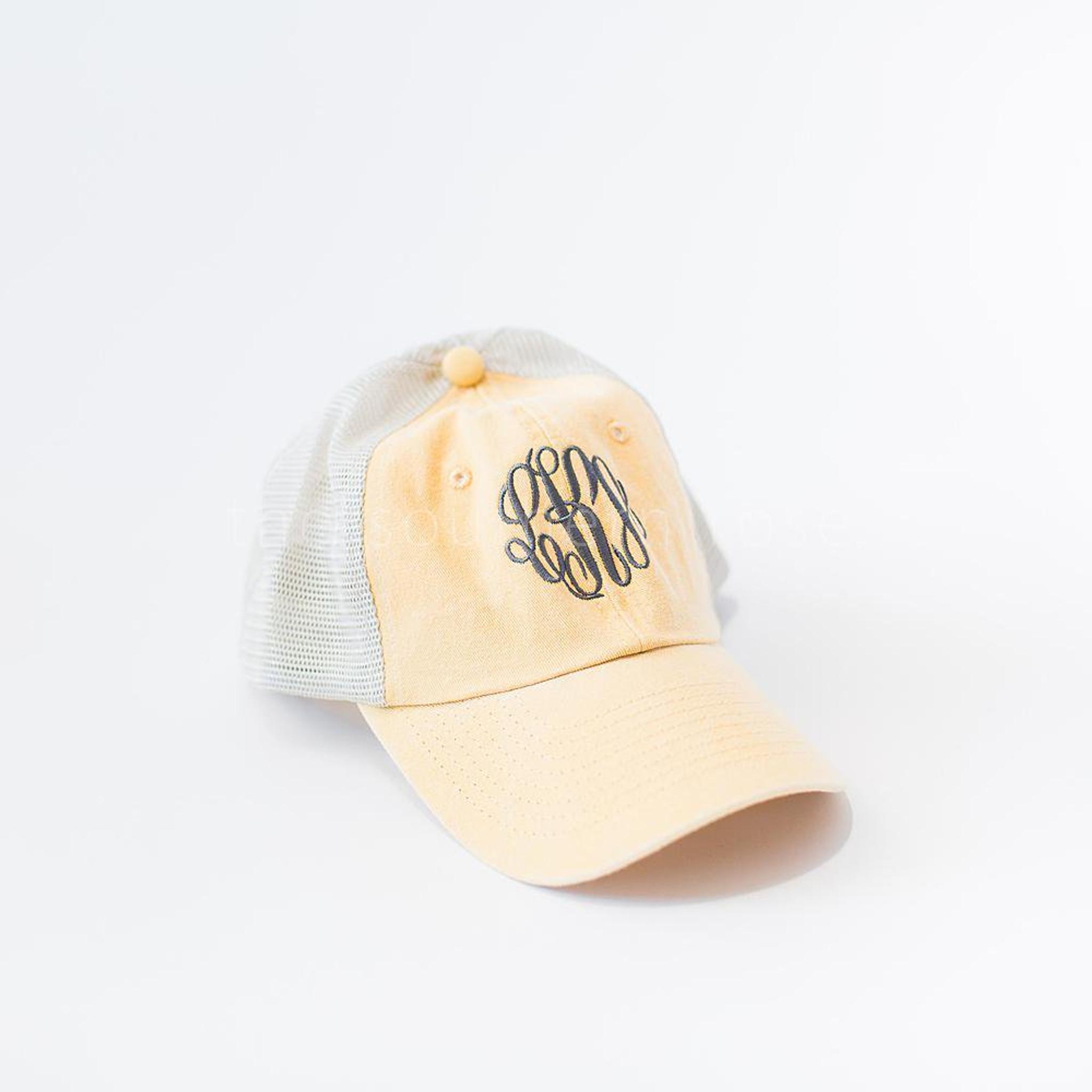 A pale yellow monogrammed trucker hat.