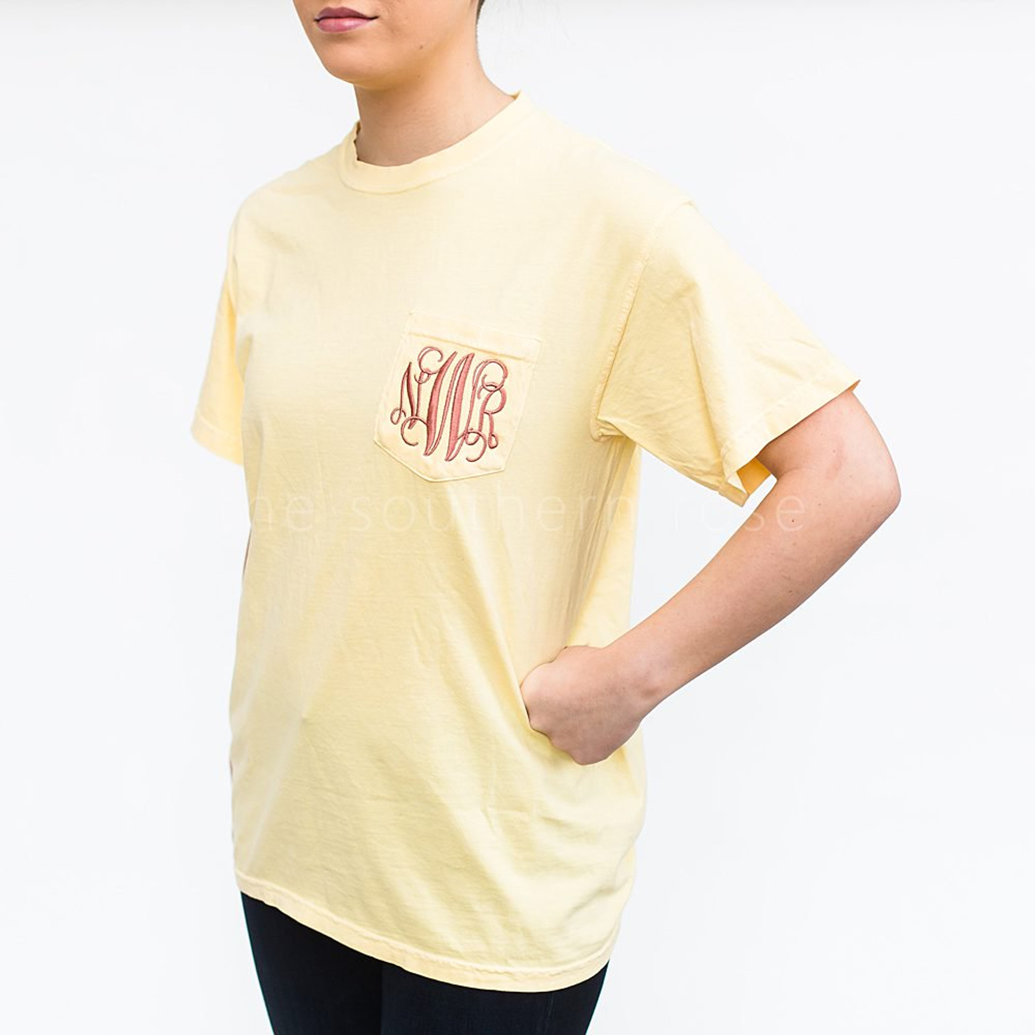 "A girl is wearing a light yellow tee shirt with the monogram ""NWR"" in fancy lettering on the chest pocket."