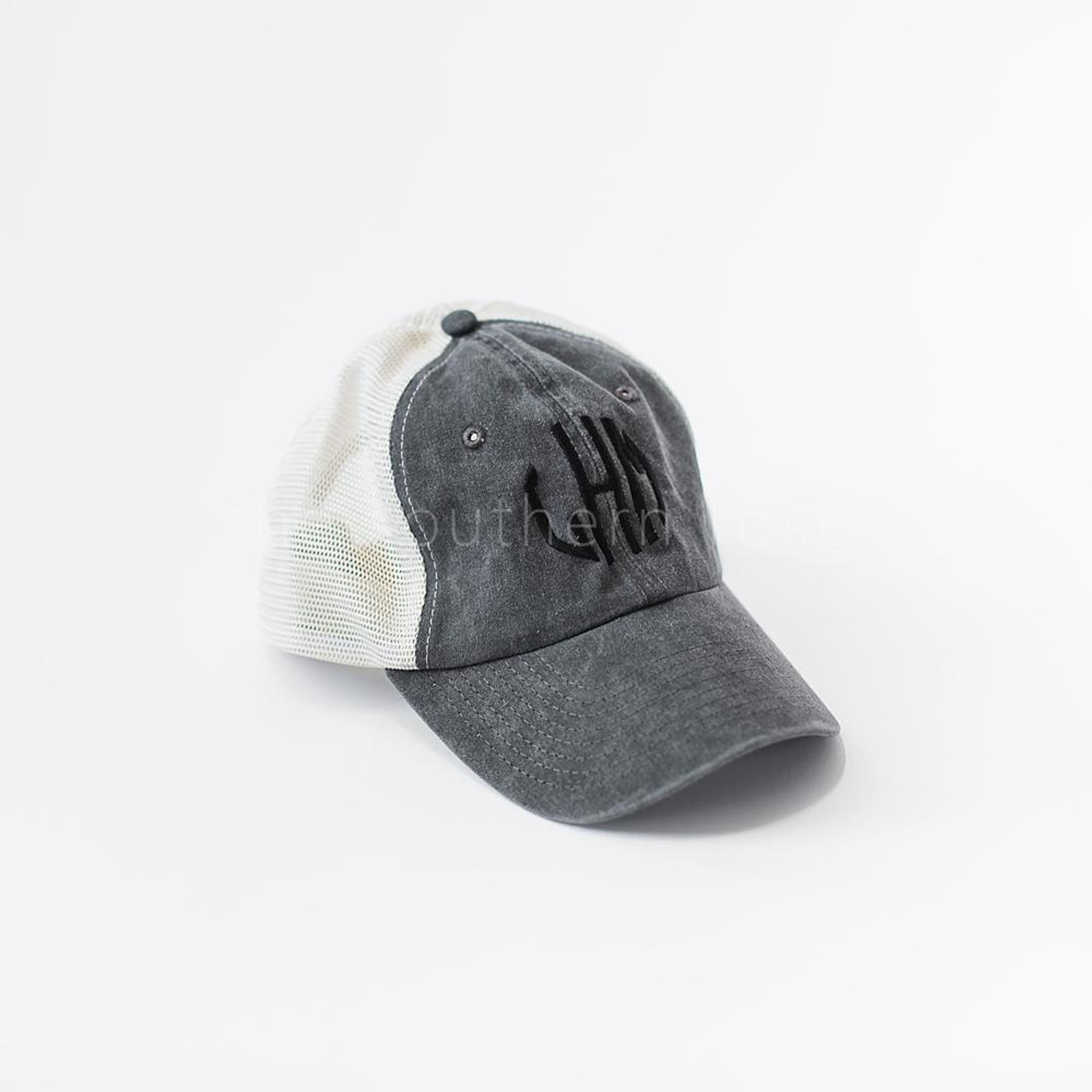 A gray and white trucker hat with black monogrammed letters.