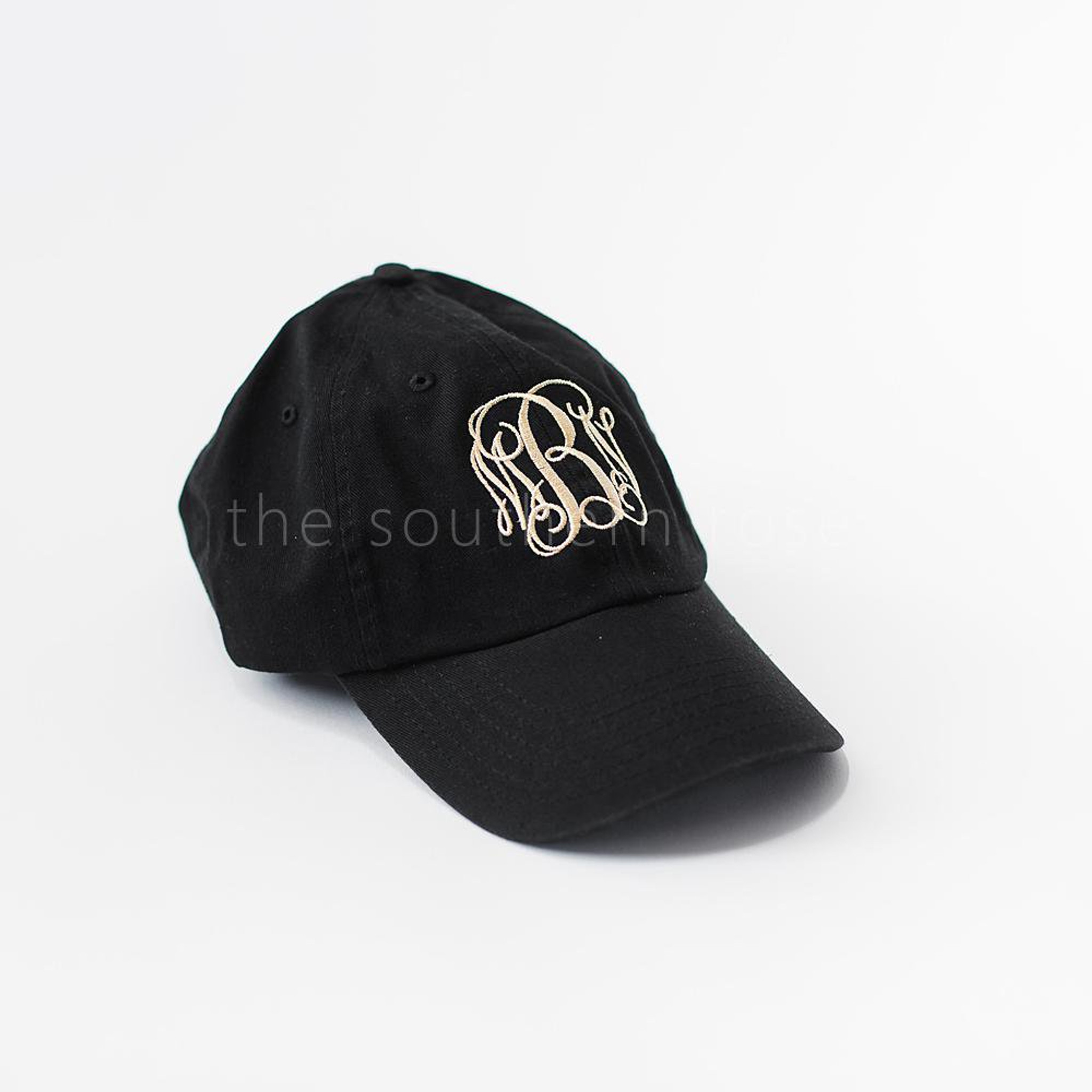 A black baseball hat with white monogrammed letters.