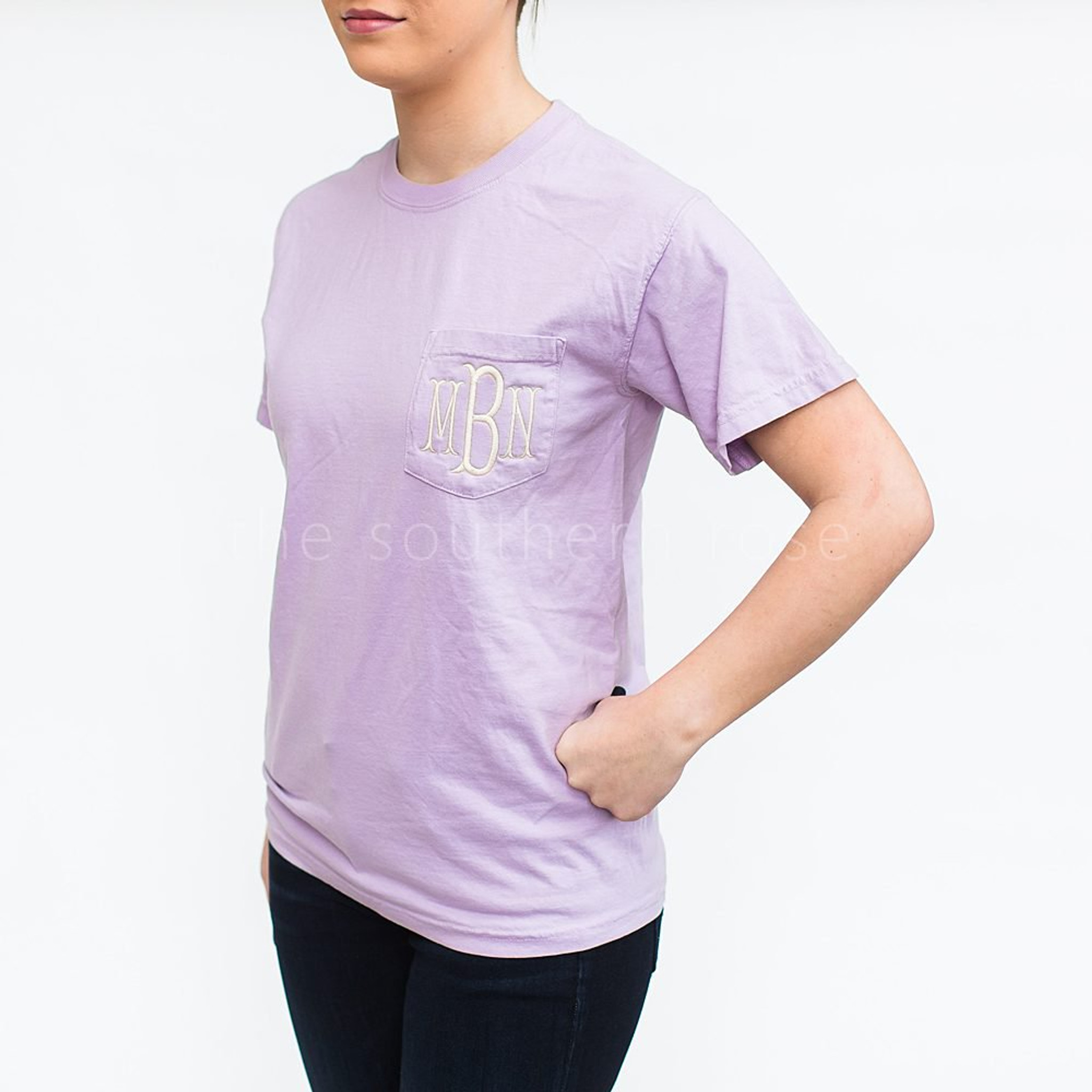 A pale purple tee shirt with monogrammed letters on the chest pocket.