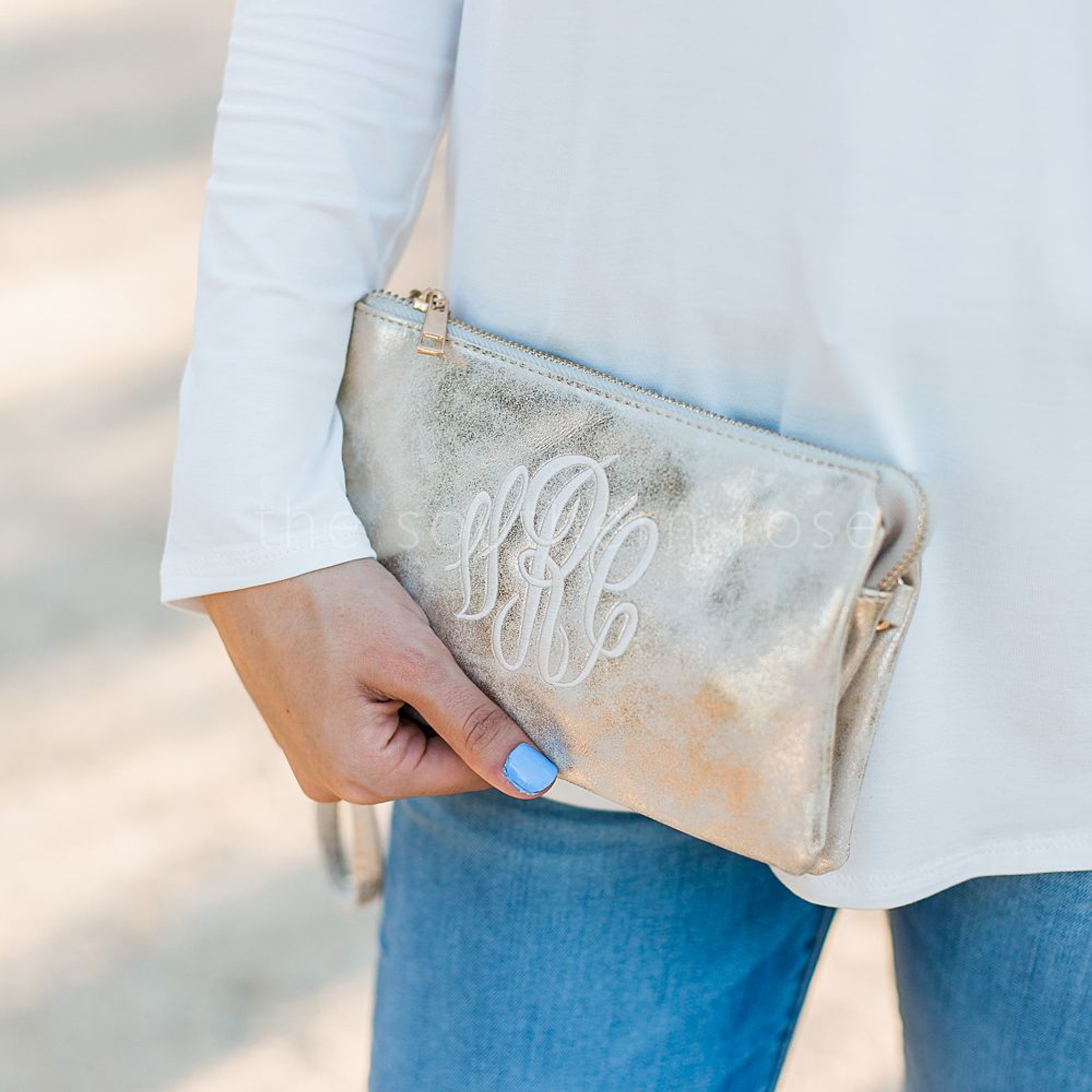 A monogrammed crossbody purse in metallic gold.