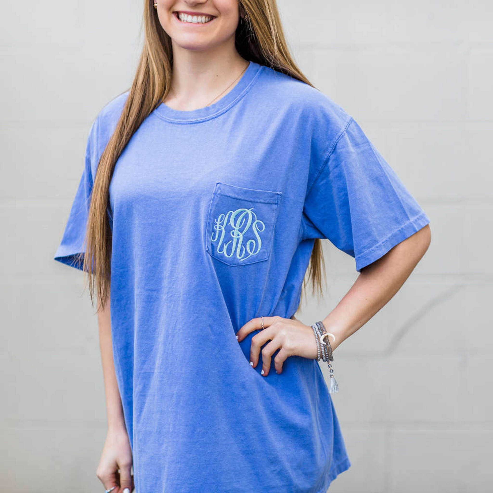 "A girl is wearing a light blue tee shirt with the monogram ""KRS"" in fancy white lettering on the chest pocket."