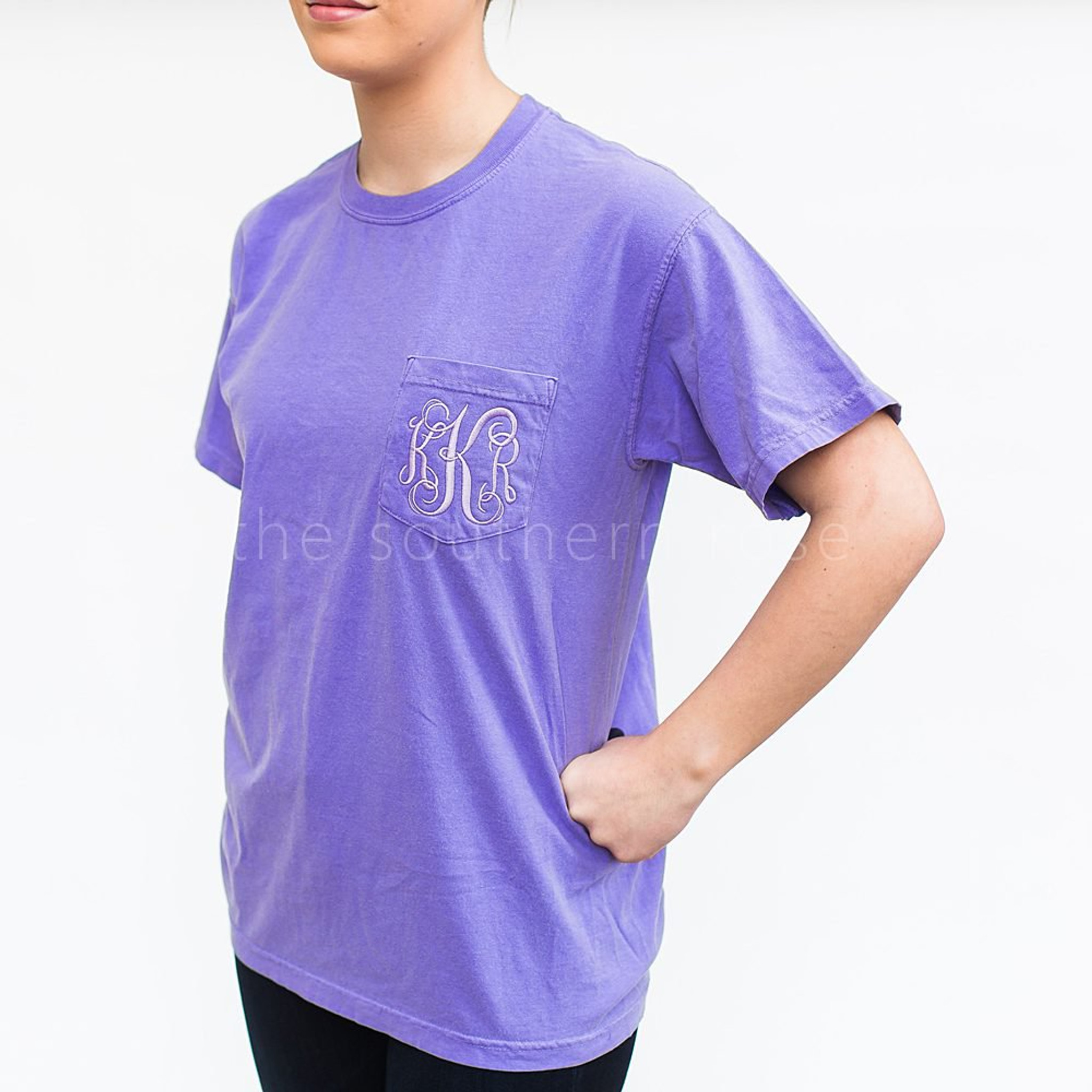 "A girl is wearing a light blue tee shirt with the monogram ""KKR"" in fancy white lettering on the chest pocket."
