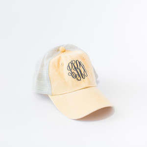 A pale yellow monogrammed trucker hat.