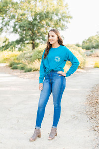 A woman stands outside wearing jeans and a teal long-sleeve shirt with fancy monogram letters on the chest pocket.