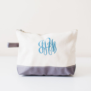 A white and gray cosmetic bag with blue monogrammed letters.