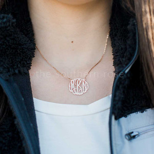 A woman wears a metal monogram necklace.