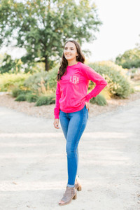A woman stands outside wearing jeans and a pink long-sleeve shirt with white monogram letters on the chest pocket.