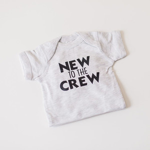 """A white textured baby onesie with the words """"NEW TO THE CREW"""" inscribed in black letters on the chest."""