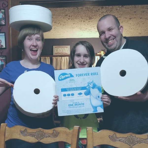Smiling Family with 2 Charmin Forever Rolls and holding the box insert