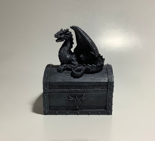 Black decorative trinket box with dragon figure on top.