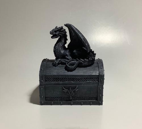Black decorative trinket box with dragon figure on top.
