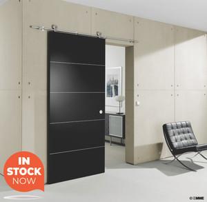 Stainless steel barn door kit installed as a bathroom door in a bedroom of a modern home