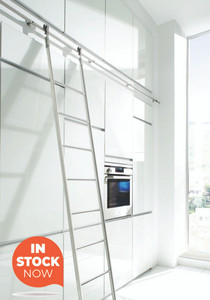 Stainless steel barn door track used for an interior sliding library ladder in a modern styled kitchen