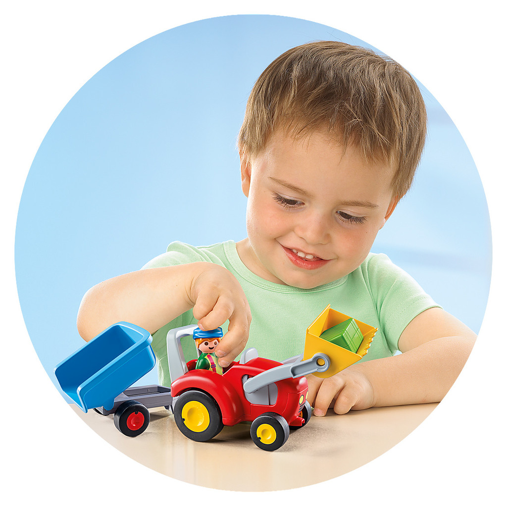 Boy playing with Playmobil Tractor with Trailer