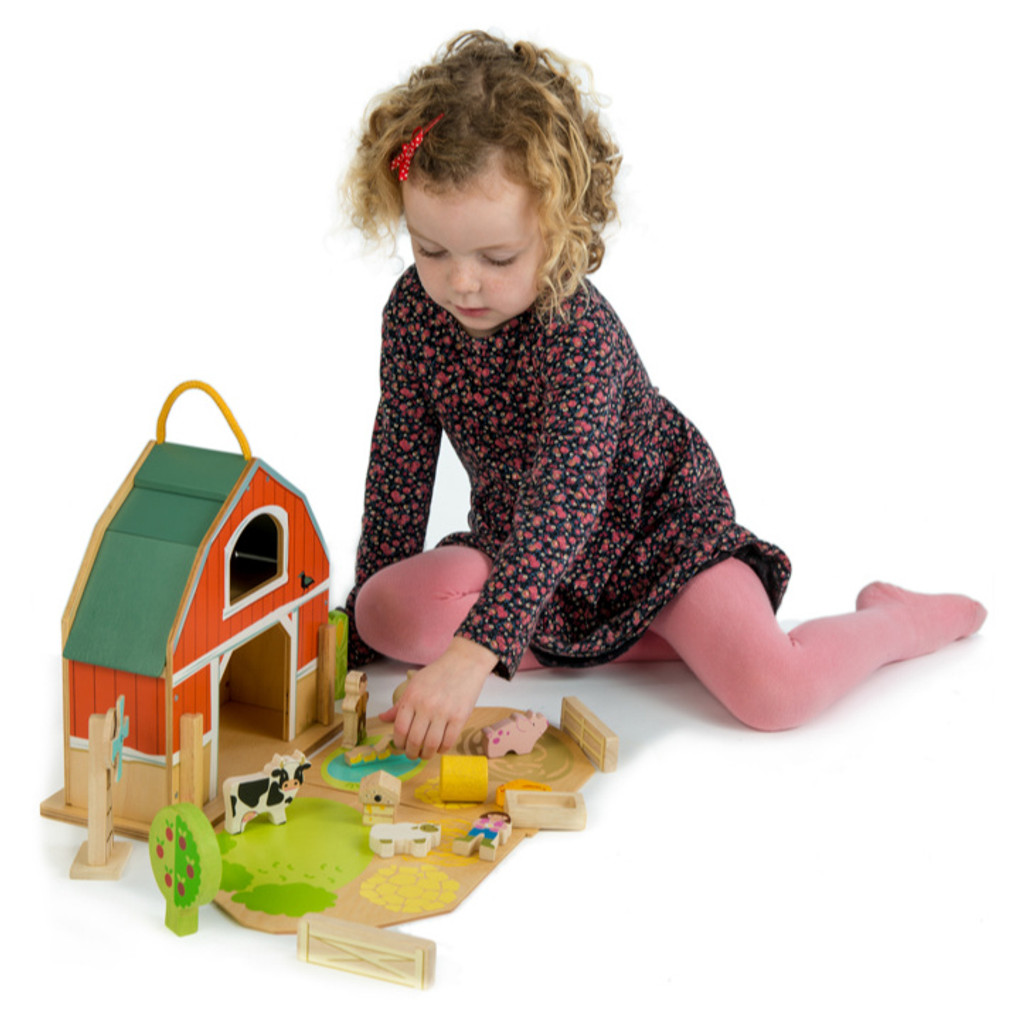 Girl playing with Tender Leaf Toys Little Barnyard Set