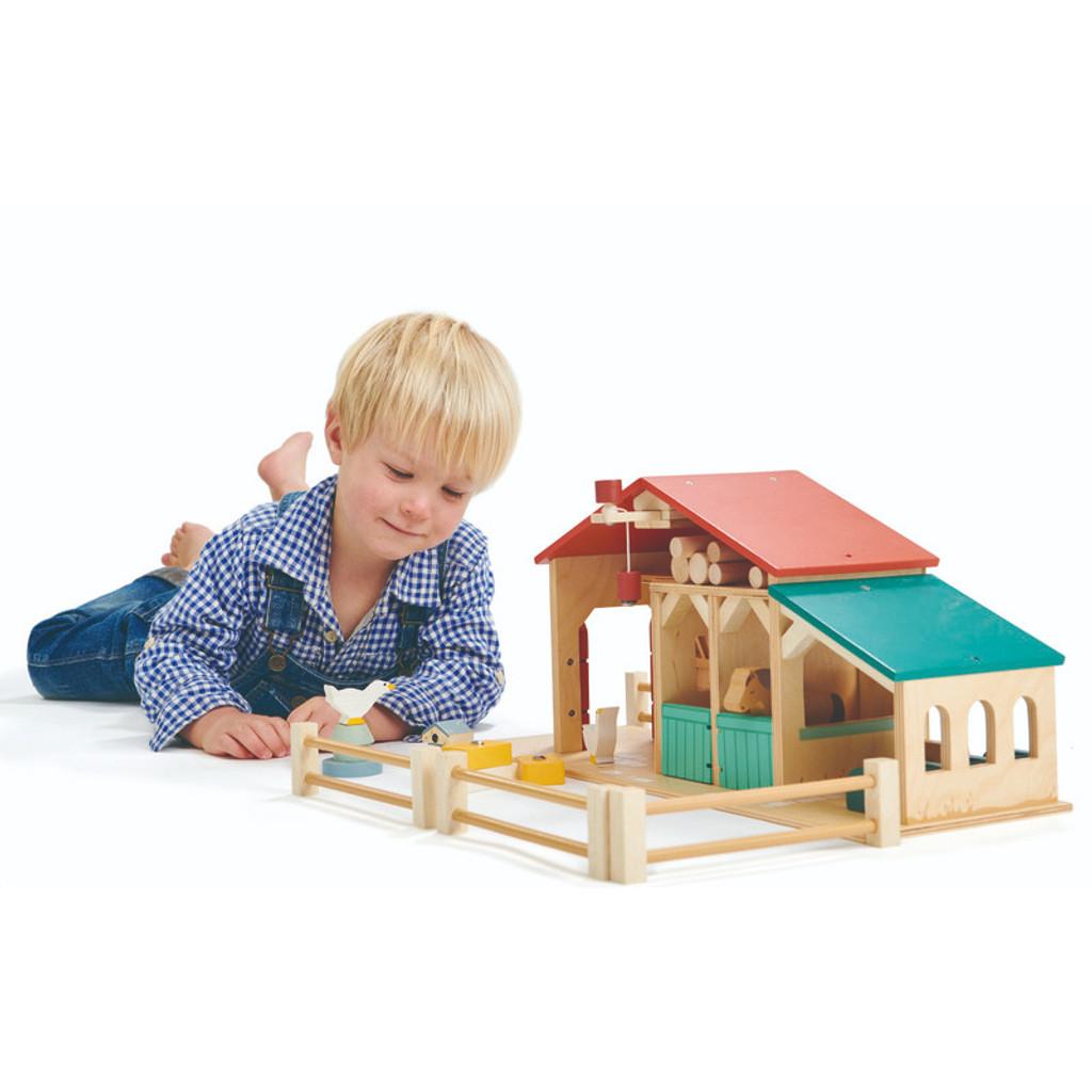 boy playing with Tender Leaf Toys Farm