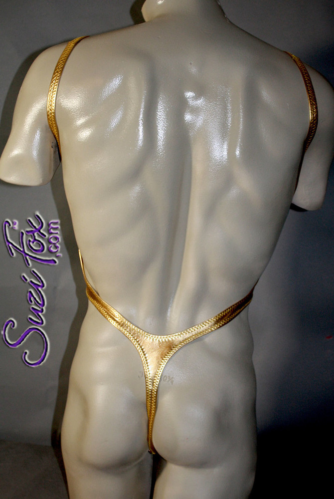 Mens One Piece T-back Thong Bodysuit shown in Gold Metallic foil Spandex, custom made by Suzi Fox. • Custom made to your measurements. • Smooth front, high leg hole, low back and t-back thong rear. • Available in any fabric on this site. • Made in the U.S.A.