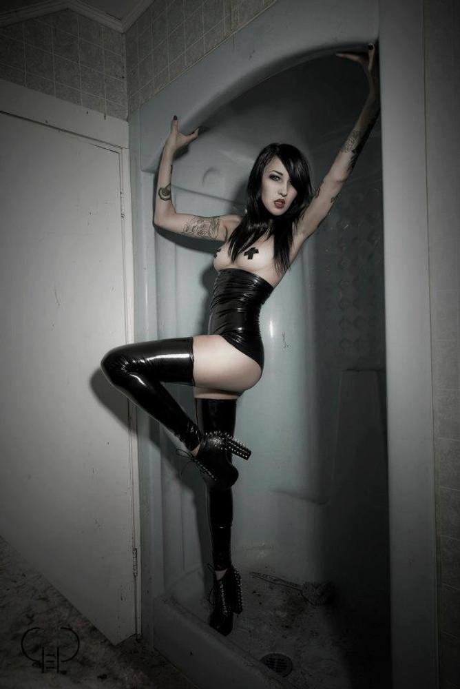 Underbust Cheeky Peeker Booty Shorts shown in Black Vinyl/PVC Spandex, custom made by Suzi Fox. Enhances the rear butt cheeks. Model: Kissa Von Adams. Photography: Greg Mohn @goodeggproductions