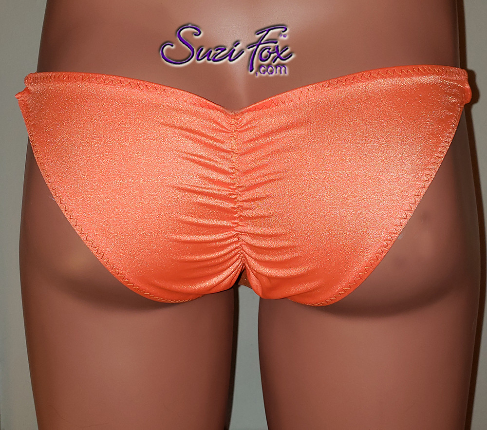 Men's Pouch Front, Skinny Strap, Gathered Tanga Bikini - shown in Neon Orange Milliskin Tricot Spandex, custom made by Suzi Fox. • Standard front height is (6 inches (15.2 cm). • Choose your pouch size! • Available in 3, 4, 5, 6, 7, 8, 9, and 10 inch front heights. • Choose any fabric on this site, including vinyl/PVC, metallic foil, metallic mystique, wetlook lycra Spandex, Milliskin Tricot Spandex. The vinyl/PVC is a latex alternative, great for people allergic to latex! • Wear it as swimwear OR underwear! • Made in the U.S.A
