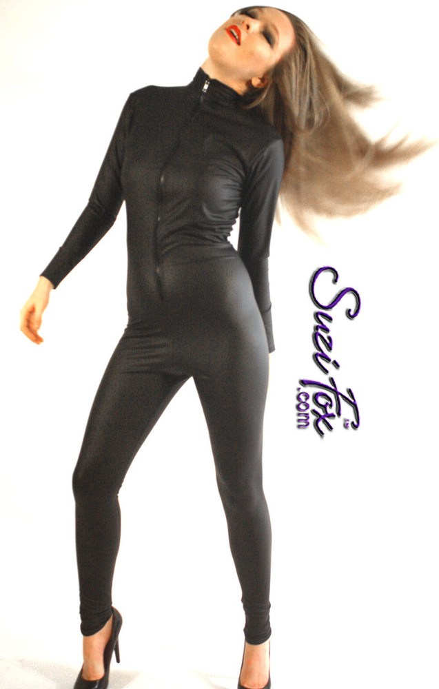 "Custom Catsuit by Suzi Fox shown in Matte Black (no shine) Vinyl/PVC coated Nylon Spandex.  Perfect for DKR Catwoman Costume. You can order this Catsuit in almost any fabric on this site.  • Available in black matte (no shine), white matte (no shine), and gloss black, red, white, light pink, neon pink, fuchsia, purple, royal blue, navy blue, turquoise, stretch vinyl coated spandex. • Your choice of front or back zipper (front zipper shown). • Optional 1 or 2-slider crotch zipper, and ""Selene"" from Underworld TS zipper, or aluminum circular slider zipper like Catwoman comic characters. • Optional wrist zippers • Optional ankle zippers • Optional finger loops • Optional rear patch pockets • Made in the U.S.A."