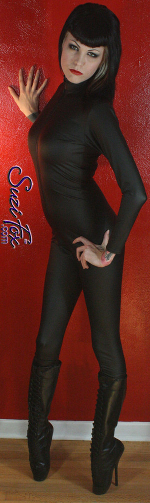 "Custom Catsuit by Suzi Fox shown in Matte Black (no shine) Vinyl/PVC coated Nylon Spandex. Shown with optional 1-slider crotch zipper. Perfect for DKR Catwoman Costume. You can order this Catsuit in almost any fabric on this site.  • Available in black matte (no shine), white matte (no shine), and gloss black, red, white, light pink, neon pink, fuchsia, purple, royal blue, navy blue, turquoise, stretch vinyl coated spandex. • Your choice of front or back zipper (front zipper shown). • Optional 1 or 2-slider crotch zipper, and ""Selene"" from Underworld TS zipper, or aluminum circular slider zipper like Catwoman comic characters. • Optional wrist zippers • Optional ankle zippers • Optional finger loops • Optional rear patch pockets • Made in the U.S.A."