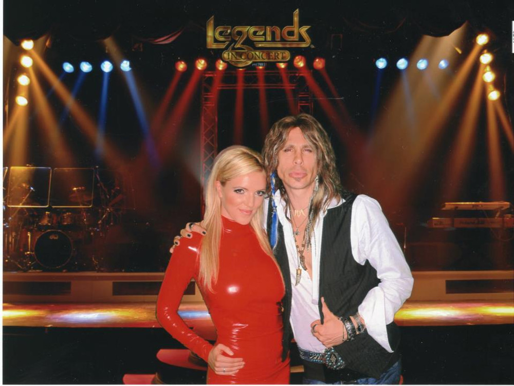 Katie Gunther Murdock as Britney Spears impersonator, wearing Suzi Fox red vinyl, smooth front catsuit, with Chris VanDahl.