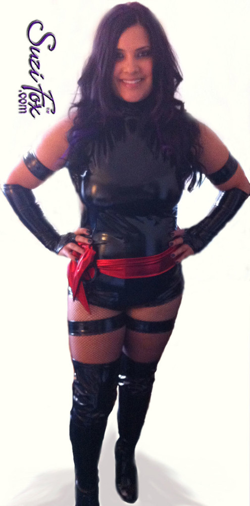 Custom Psylocke Costume shown in gloss Black Vinyl/PVC, custom made by Suzi Fox.  Costume includes 4 arm bands, 4 leg garters, bird finger gloves, red sash. • Available in gloss black, white, red, neon pink, light pink, fuchsia, purple, royal blue, navy blue, turquoise; matte (no shine) black, matte (no shine) white. This fabric is a 4-way stretch, vinyl/PVC coated spandex. • Plus size available. • Your choice of rears - French legs (Rio), or Cheeky. • Made in the U.S.A.