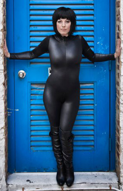 "Customer Picture! Custom Catsuit by Suzi Fox shown in Black Wet Look Lycra Spandex.  Photo by Russ Watkins. You can order this Catsuit in almost any fabric on this site.  • Available in black, red, white, turquoise, navy blue, hot pink, lime green, green, yellow, royal blue, steel gray, neon orange. This is a 4-way stretch fabric with a medium shine. • Your choice of front or back zipper (front zipper shown). • Optional 1 or 2-slider crotch zipper, and ""Selene"" from Underworld TS Brass zipper, or aluminum circular slider zipper like Catwoman comic characters. • Optional wrist zippers • Optional ankle zippers • Optional finger loops • Optional rear patch pockets • Made in the U.S.A."