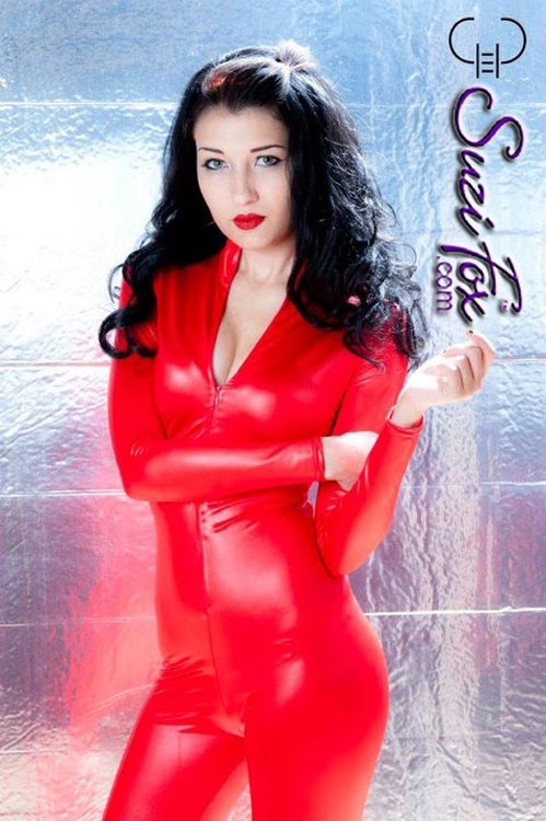 """Custom Catsuit by Suzi Fox shown in Red Wet Look Lycra Spandex.  You can order this Catsuit in almost any fabric on this site.  • Available in black, red, white, turquoise, navy blue, hot pink, lime green, green, yellow, royal blue, steel gray, neon orange. This is a 4-way stretch fabric with a medium shine. • Your choice of front or back zipper (front zipper shown). • Optional 1 or 2-slider crotch zipper, and """"Selene"""" from Underworld TS Brass zipper, or aluminum circular slider zipper like Catwoman comic characters. • Optional wrist zippers • Optional ankle zippers • Optional finger loops • Optional rear patch pockets • Made in the U.S.A. Photo by Gregory Mohn"""