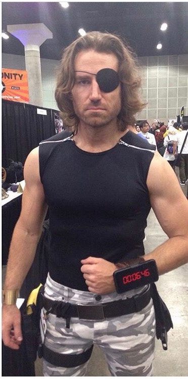 Snake Plissken style shirt as seen in the movie 'Escape From New York', custom made by Suzi Fox. Fabric shown is black wet look lycra spandex. • 2 separating zippers at the shoulders. Aluminum is standard. • Free custom sizing! • Standard shirt length for XXS-Medium, from shoulder to hem, is 24 inches (61 cm), Large-6X is 27 inches (68.6 cm) Made in the U.S.A. CUSTOMER PICTURE! Thanks to Byrne Owens!
