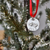 Hand stamped double heart ornament, shown hanging on a tree. Ornament is made with fine pewter, hung on a red ribbon, with 2 raised hearts, and the year stamped on the bottom.