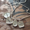 Sterling silver hand stamped mother's necklace with raised edge charms, shown close up on wood