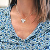 Model wearing fine silver Mini Squares personalized necklace, each square hand stamped with a name and with an embedded birthstone