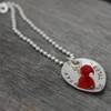 Side view of custom silver Scooped Teardrop with Stone Necklace, personalized with hand stamped Kyle and Tyler and a star, and a red crystal birthstone, shown on wood