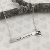 "lower case typewriter font on custom silver Bar Necklace, hand stamped with ""Unfinished"", shown close up on white"